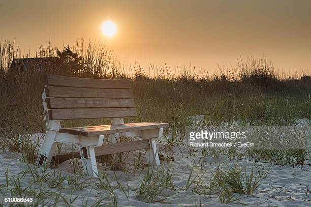 Wooden Bench On Beach Against Sky During Sunset