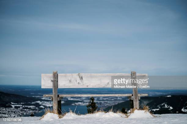wooden bench on snow covered land against sky - tegernsee stock pictures, royalty-free photos & images