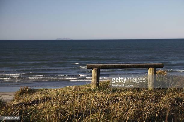 Wooden bench seat overlooking a beach