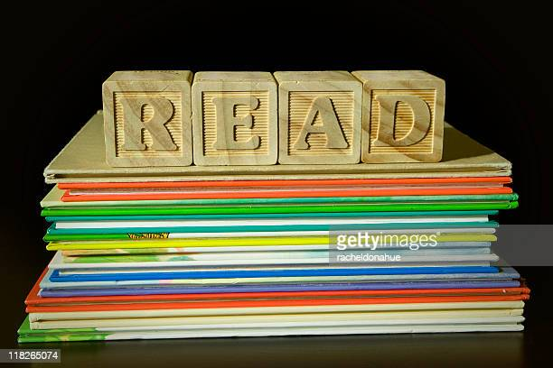 Wooden blocks spelling READ on top of pile of books