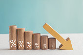 Wooden blocks with percentage sign and down arrow, financial recession crisis, interest rate decline, risk management concept