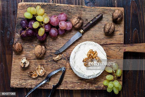 wooden board with camembert, walnuts and grapes - camembert stock photos and pictures