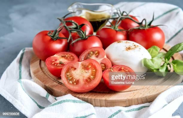 Wooden board with mozzarella tomatoes basil Italian cuisine Olive oil Close up