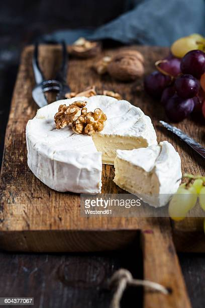 wooden board with sliced camembert, walnuts and grapes - camembert stock photos and pictures