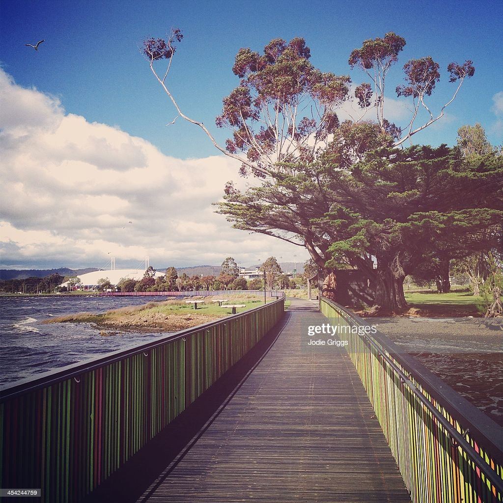Wooden boardwalk beside river with colorful rails : Stock Photo