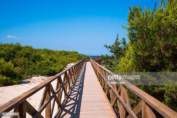 wooden boardwalk leading to playa de muro beach - muro stock photos and pictures