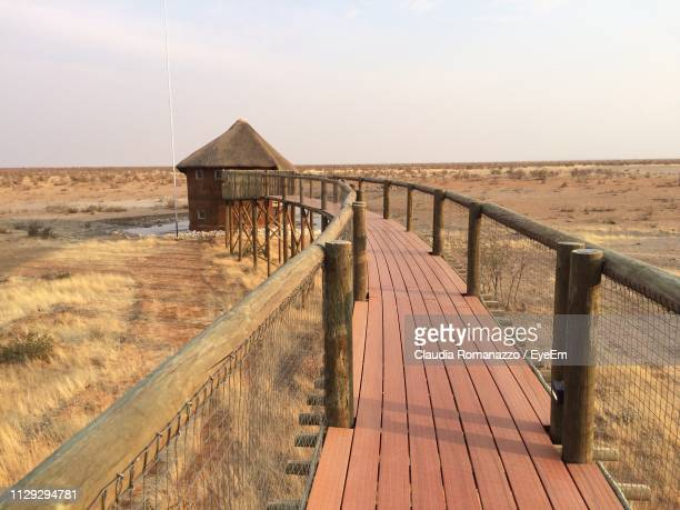 wooden boardwalk on field against clear sky - claudia romanazzo foto e immagini stock