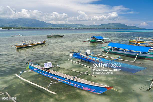 wooden boat anchored in beach with wonderful background, ampana, indonesia - central sulawesi stock pictures, royalty-free photos & images
