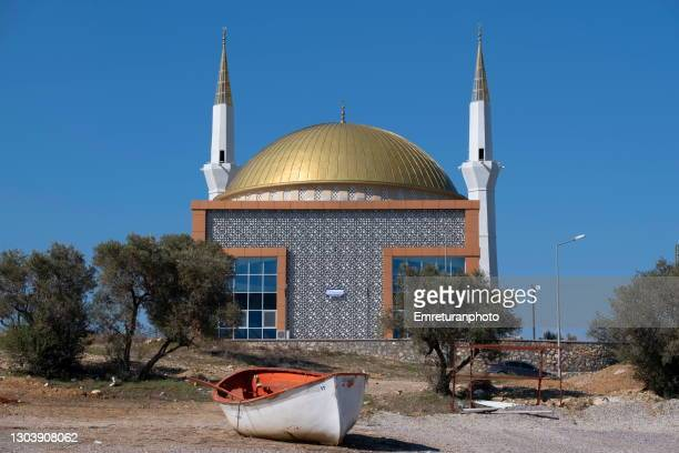 wooden boat and mosque on a sunny day at kemalpasa. - emreturanphoto stock pictures, royalty-free photos & images