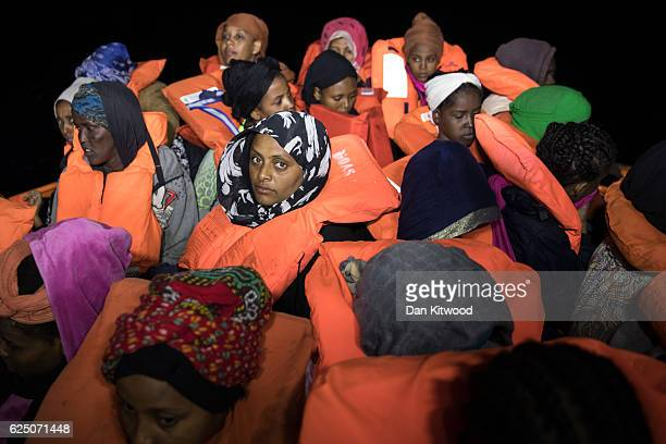 A wooden boat carrying refugees and migrants waits to be escorted to the Topaz Responder as members of MOAS Migrant Offshore Aid Station make rescues...