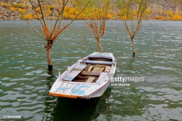 wooden boat in a lake in autumn season. - skardu stock pictures, royalty-free photos & images
