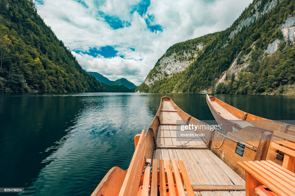 Wooden boat on a lake reflection with mountains and clouds and blue sky. Tranquil nature landscape for inspirational ideas : Stock Photo