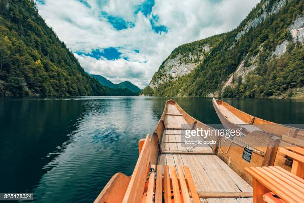 Wooden boat on a lake reflection with mountains and clouds and blue sky. Tranquil nature landscape for inspirational ideas