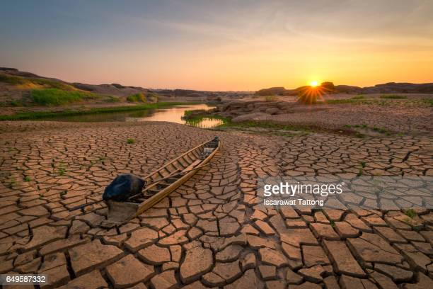 Wooden boat on drought land with sunrise