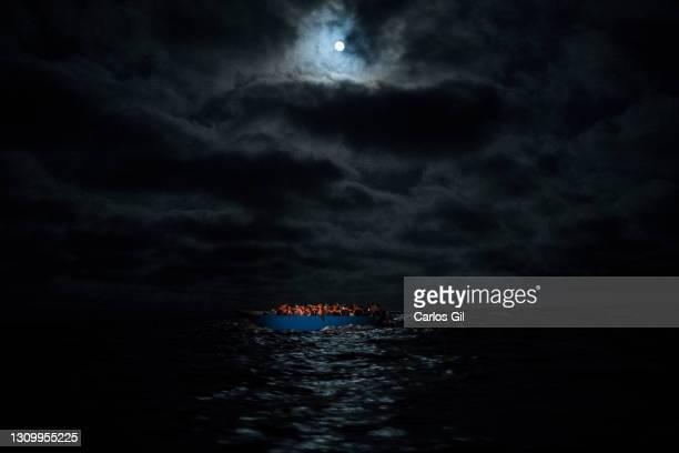 Wooden boat with approximately 100 people of different nationalities on its journey through the Mediterranean to Lampedusa, illuminated by a...