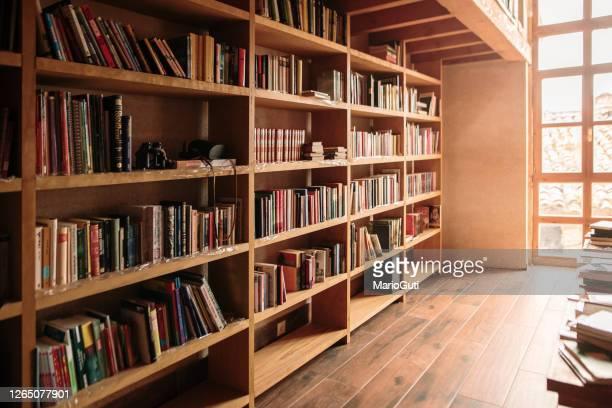 houten boekenplanken die met boeken worden gevuld - boekenplank stockfoto's en -beelden