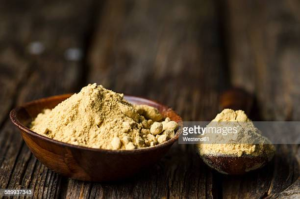 Wooden bowl and spoon with ginger powder on dark wood