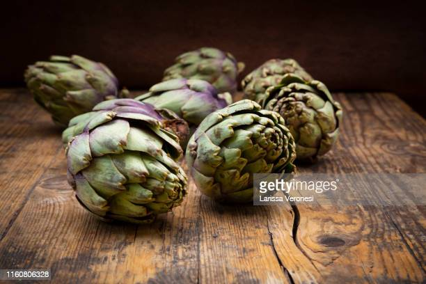 wooden bowl of organic artichokes - larissa veronesi stock-fotos und bilder