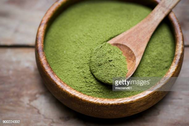 wooden bowl of organic moringa powder - moringa tree stock photos and pictures