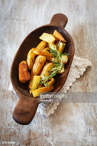 Wooden bowl of potato wedges with rosemary