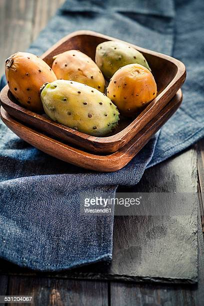 Wooden bowl of prickly pears on cloth and slate