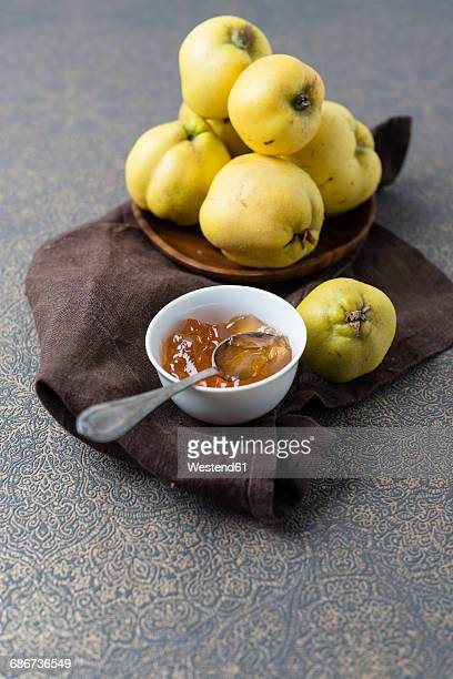 Wooden bowl of quinces and bowl of quince jelly