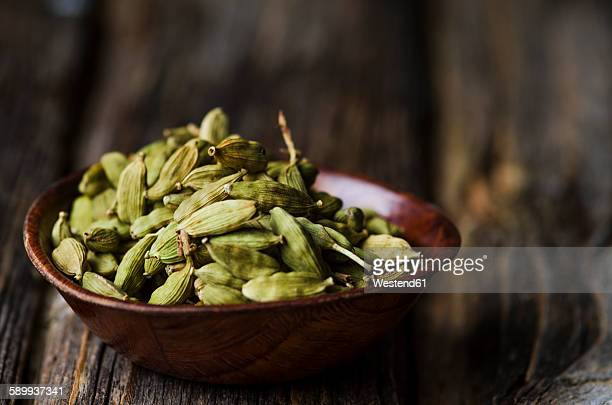 Wooden bowl with cardamom capsules