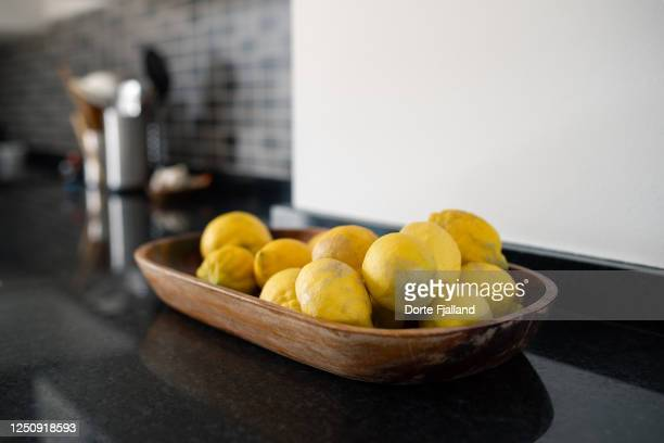 wooden bowl with lemons on a black kitchen counter - dorte fjalland stock pictures, royalty-free photos & images