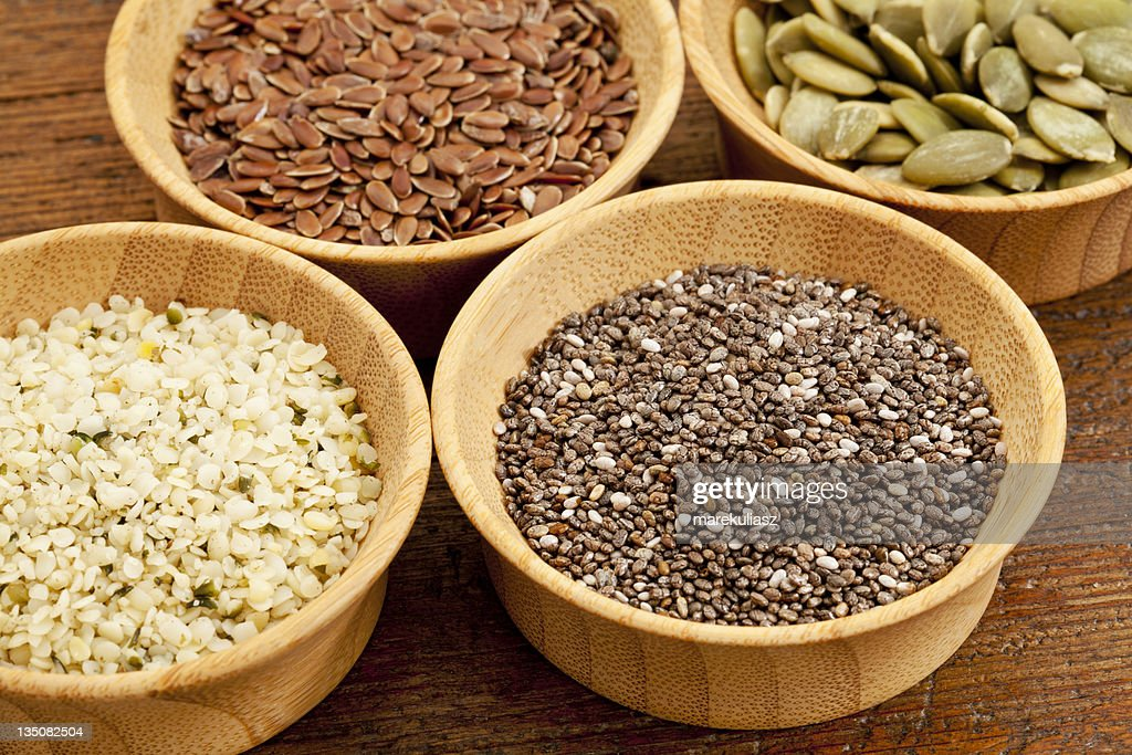 Wooden bowls of chia, hemp, flax and pumpkin seeds