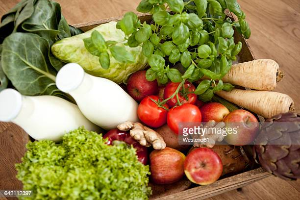 Wooden box of fresh vegetables and two bottles of milk
