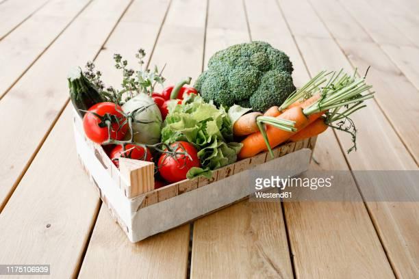 wooden box of organic vegetables on wooden floor - gemüse stock-fotos und bilder