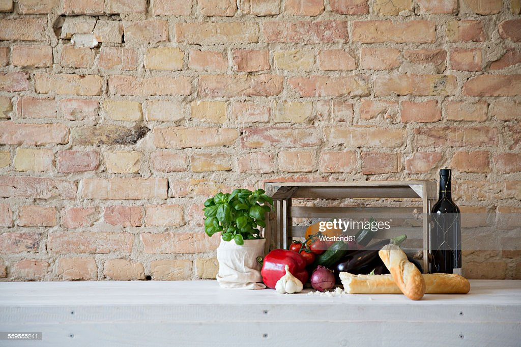 Wooden box with vegetables, baguette, basil and wine bottle : Stock-Foto
