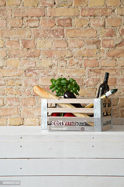 Wooden box with vegetables, pasta, baguette, basil and wine bottle