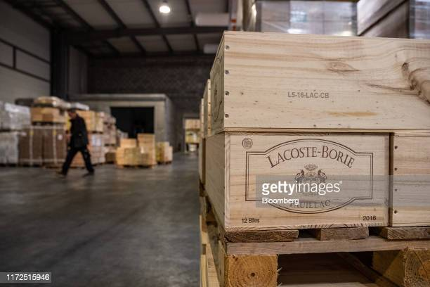 Wooden boxes of LacosteBorie Pauillac red wine sit on a pallet inside a JF Hillebrand Group AG wine storage and transit logistics warehouse in...
