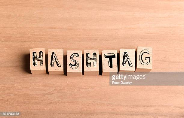 Wooden bricks spelling out word hashtag