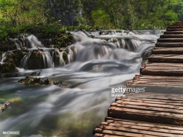 wooden bridge above waterfalls