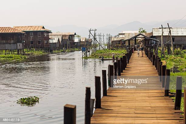 wooden bridge connecting village and land - merten snijders stockfoto's en -beelden