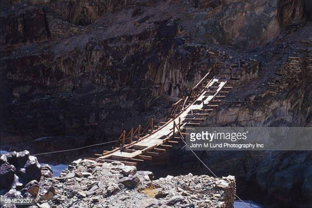 Wooden bridge in construction over rocky canyon