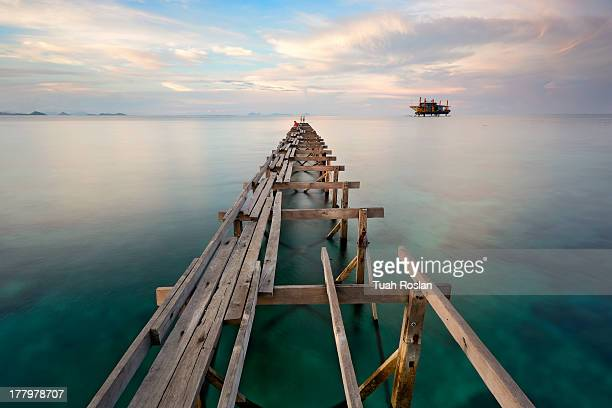 wooden bridge in the port between sunset - mabul island stock photos and pictures