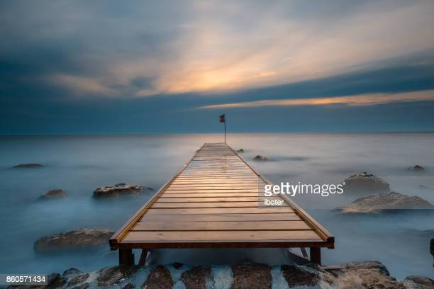 wooden bridge laying to the sea at sunrise - incidental people stock pictures, royalty-free photos & images