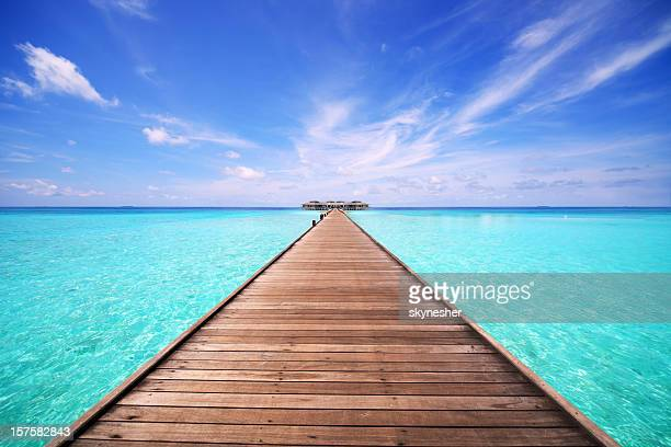 Wooden bridge leading to the bungalow on water.