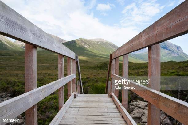 wooden bridge over allt dearg mor with a view towards glen sligachan, isle of skye, scotland, united kingdom - glen sligachan photos et images de collection