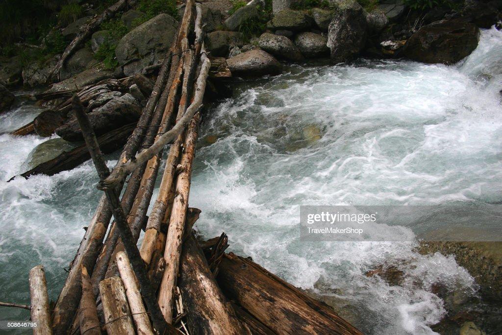 Wooden bridge over mountain the river. : Stock Photo