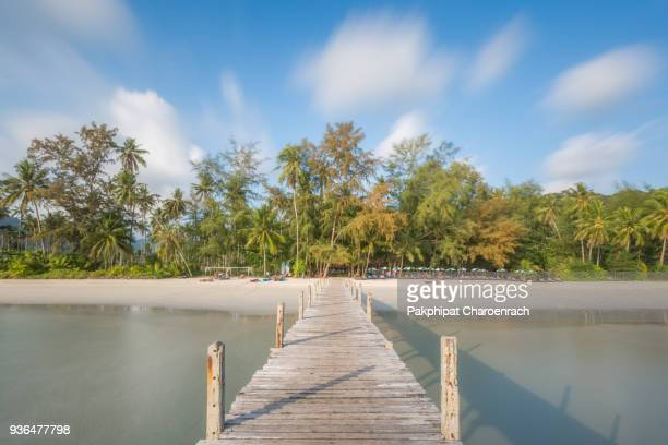 Wooden bridge pier into the beautiful beach background.