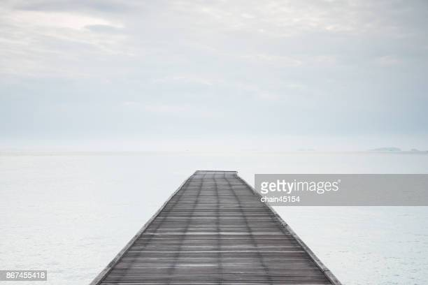Wooden bridge to the sea to a travel destination or Concept of straight way for business and new career start to foward.