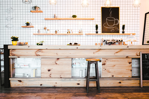wooden brown bar counter with plants and cupcakes, drawing on shelf in coffee house 1159599533