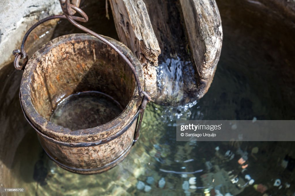 Wooden bucket and gutter on a well : Stock Photo