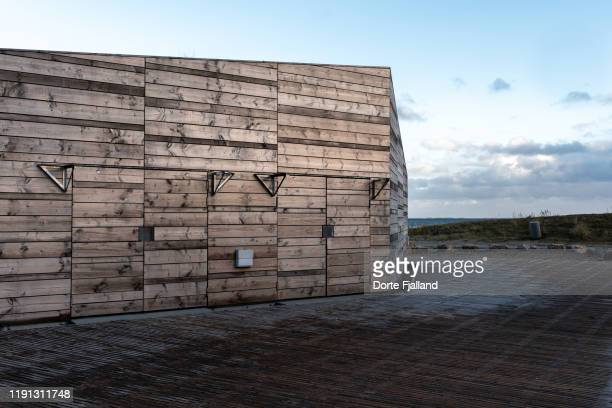 wooden building with afternoon sun on the wall and an empty background with a blue sky and a glimpse of a blue sea - dorte fjalland stock-fotos und bilder