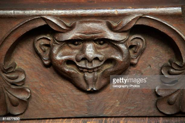 Wooden carved devil face in bench seat Ufford church Suffolk England UK
