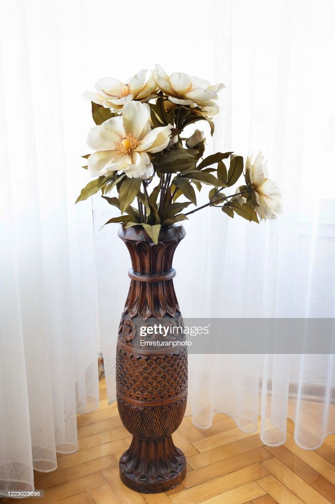 Wooden carved vase with artifical flowers in daylight. : Stock Photo